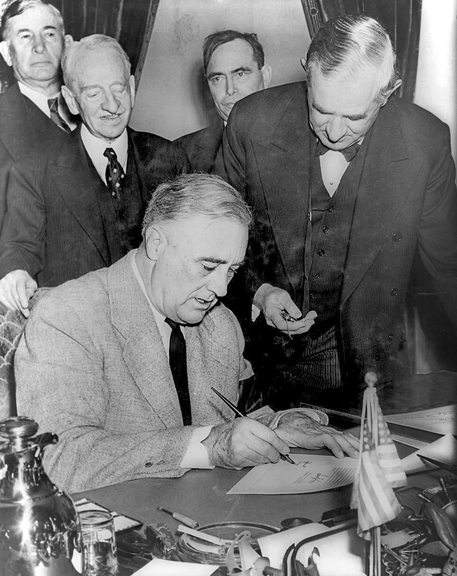 President Franklin D. Roosevelt signing the declaration of war against Germany, marking US entry into World War II in Europe. Senator Tom Connally stands by holding a watch to fix the exact time of the declaration. December 11, 1941.