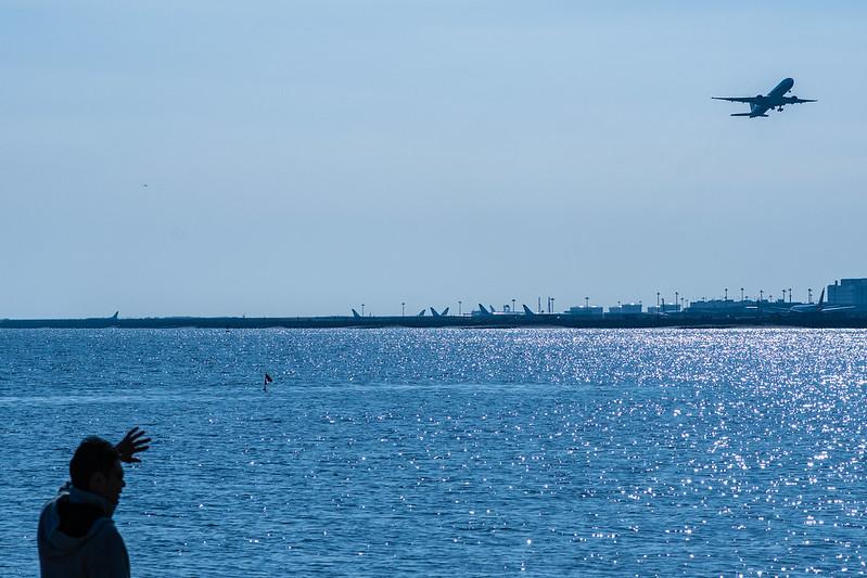 飛行機を見る男性と離陸する飛行機