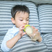 Portrait of a baby boy drinking from bottle on bed at home