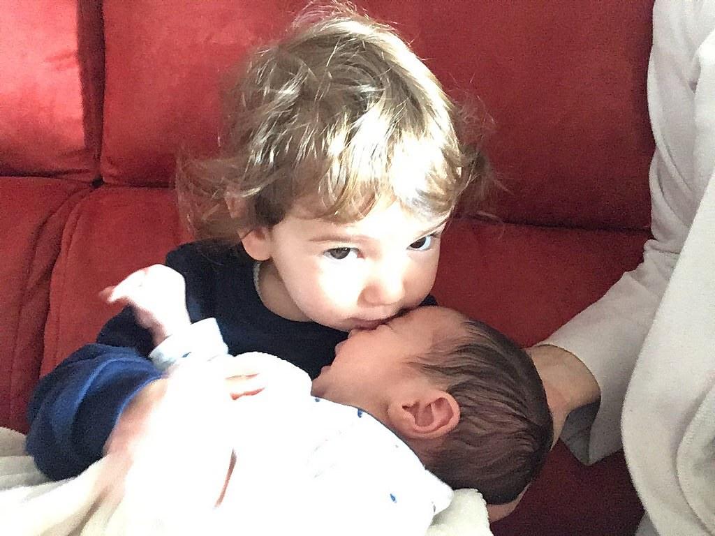 Cogiendo a su hermano recién nacido