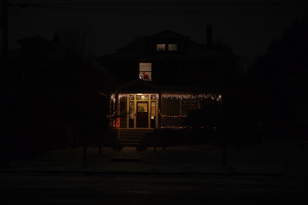 A figure can be seen in an upstairs window in a house decorated with Christmas lights