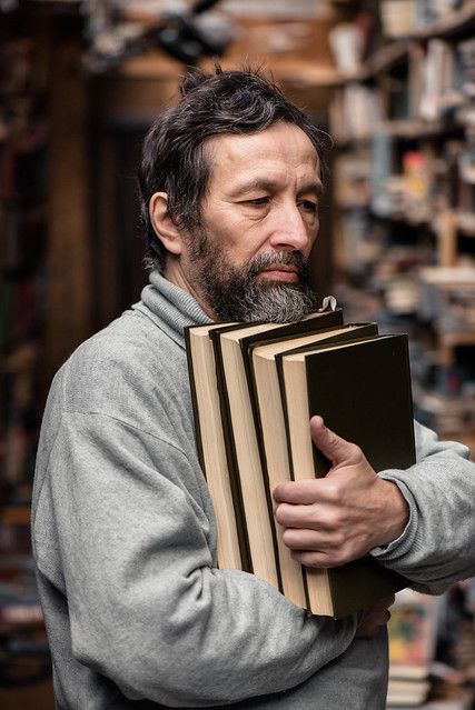 Portrait of authentic senior man on book market