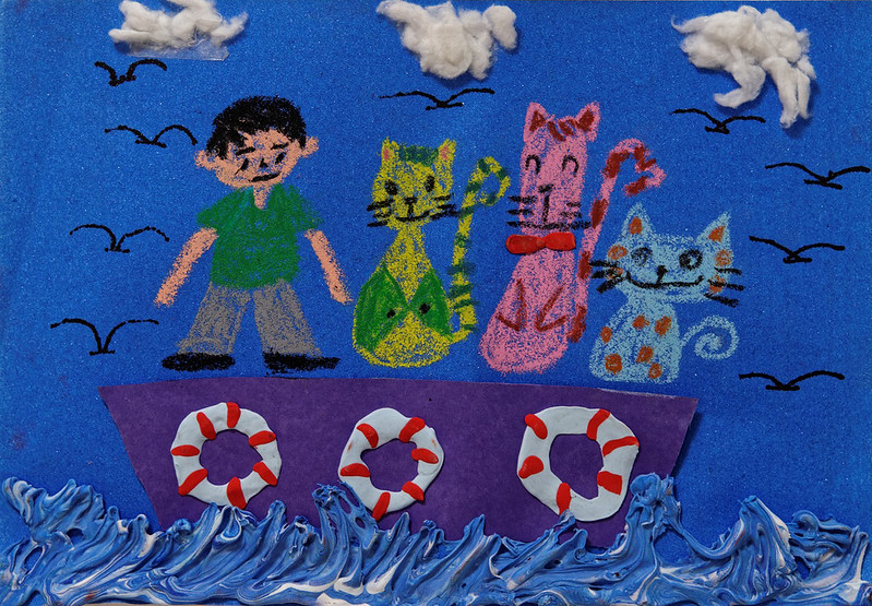A little boy with his cat friends on a boat