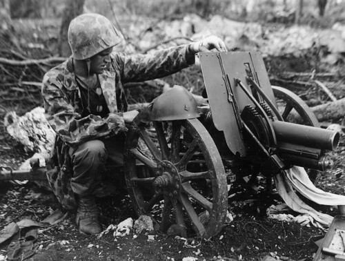 Private 2-nd Division US Marine Corps James Swick with a captured  Japanese 70 mm Type 92 howitzer on the island of Saipan july 1944.