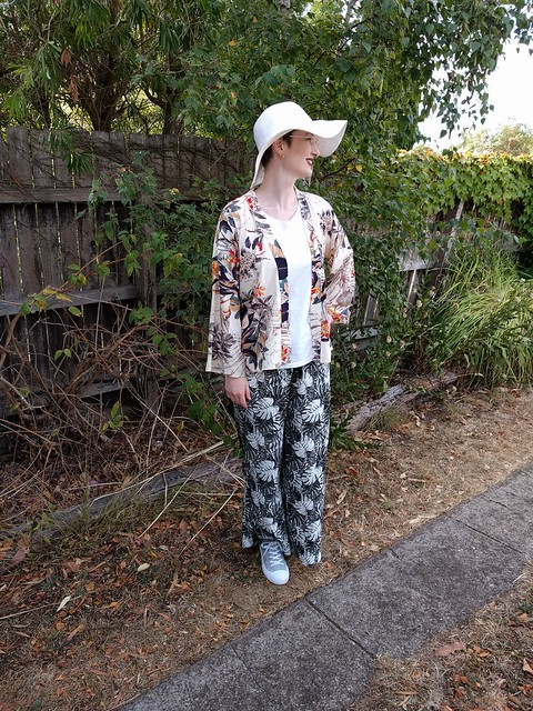A woman stands in front of a garden fence. She wears a neutral print kimono jacket, wide sunhat, white tee and rayon fern print pants.