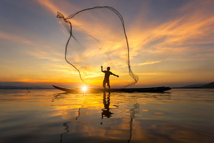 Silhouette of Myanmar fisherman on wooden boat ,Myanmar fisherman in action catching freshwater fish in nature river, Myanmar traditional fishermen at the sunset near Inle lake,Myanmar