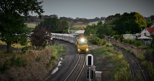 With the setting sun dropping below the horzion, NR99+G530 bring #4SA8 Sydney to Perth Indian Pacific passenger service through the former station at Newbridge, NSW.