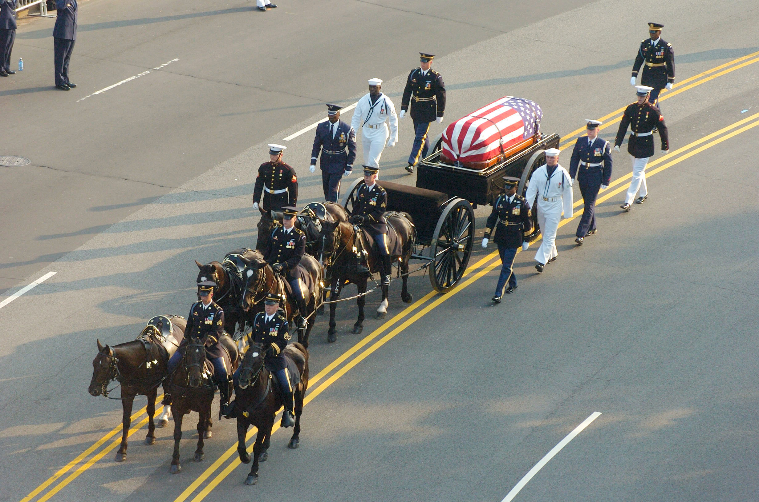 Members of a joint honor guard escort the Army's 3rd U.S. Infantry Regiment Old Guard Caisson Platoon bearing former President Ronald Reagan's flag draped casket making its way down Constitution Ave. during President Reagan's funeral procession from the White House to the U.S. Capitol, Washington, D.C, June 9, 2004