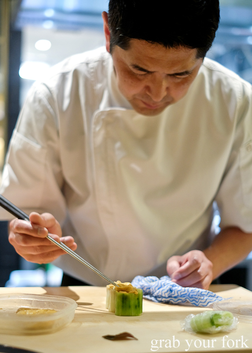 Chef Ryuichi Yoshii placing sea urchin roe into cucumber wrapped sushi at Fujisaki by Lotus at Barangaroo in Sydney
