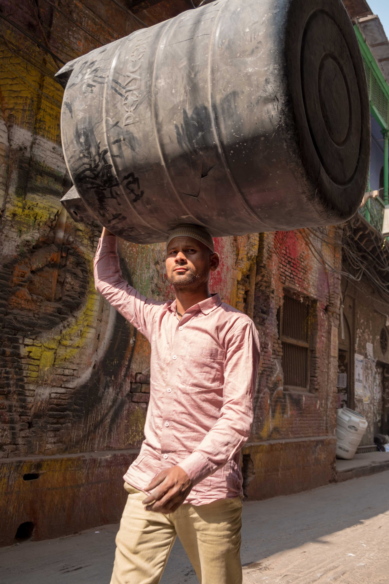 A labourer carrying a old water tank