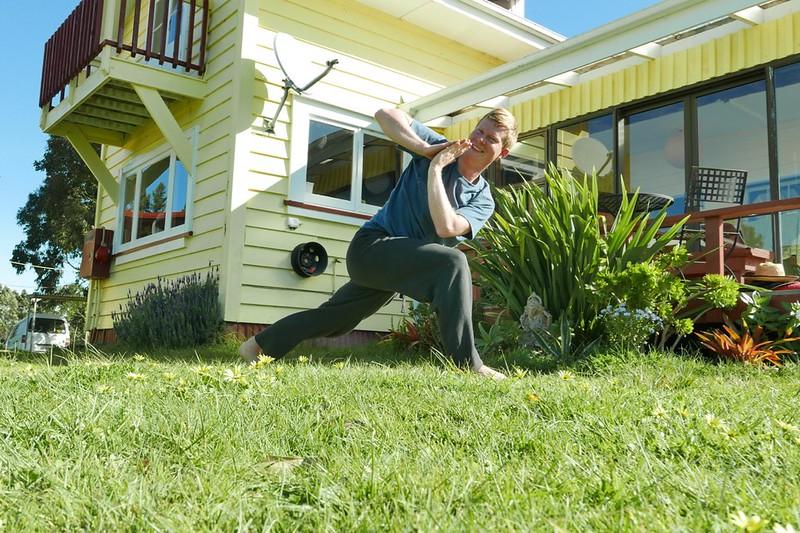 """Micha verrenkt sich bei feinstem """"Winter""""-Wetter im Garten vor dem Gästehaus im Garten."""