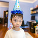 Portrait of a baby boy wearing a party hat and looking at camera at home