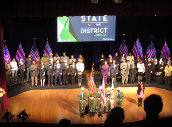 Audience member silhouettes are visible in front of a stage, where the mayor and other District officials stand while several people in military dress stand by the U.S. and D.C. flags.