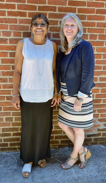 The executive director of New Endeavors by Wome and the executive director of Calvary Women's Services stand side-by-side in front of a brick wall.