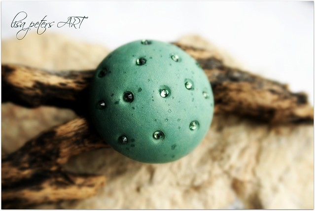 green cabochon with crystals