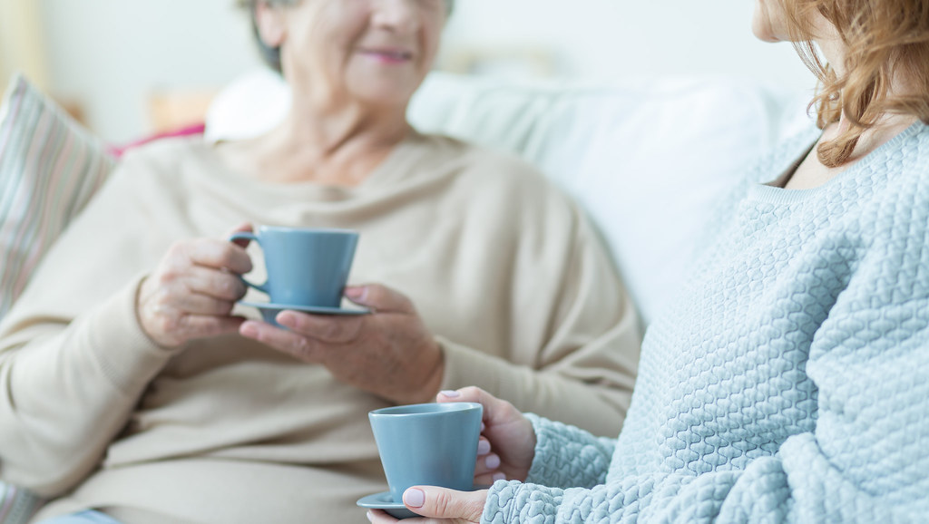 An elderly woman and middle aged woman sit, drinking tea