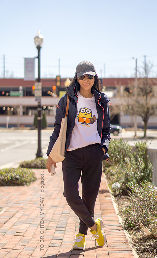 gray baseball cap, navy windcheater jacket, minions graphic tee, canvas tote, navy sweatpants, yellow sneakers