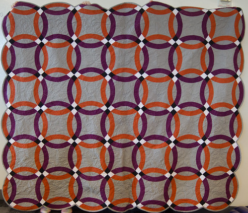 This is the project code-named 'Orangerie.' Since orange and purple were Robert and Aidan's wedding colors, I chose orange and purple shot cottons for the rings. I had to tone the grey down a couple of notches, and use a Kona solid ('pewter') to let both the orange and the purple rings have room to talk. Since Robert and Aidan are Australian, the backing is an orange-pink-purple Aboriginal print.  I had to be unusually careful about accuracy on these rings, because shot cottons do love to stretch and wobble, and those black-and-white ring intersections were absolutely unforgiving. Any inaccuracy showed. But hey, that's what pins are for.  Quilting by the always-lovely Nancy of Just Quilting PDX.