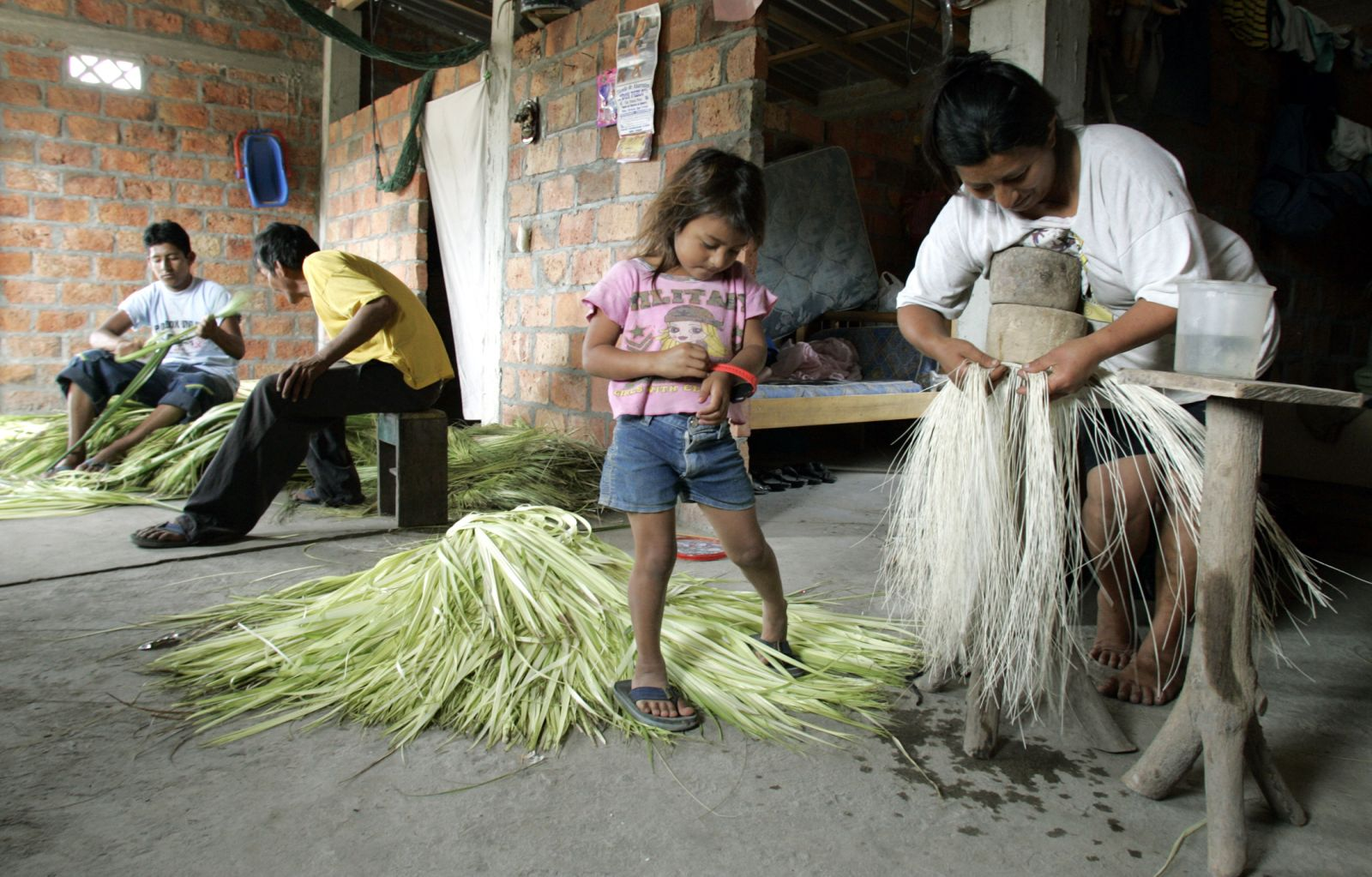 Weavers at work turning toquilla straw into hats. (Reuters/Guillermo Grunja)
