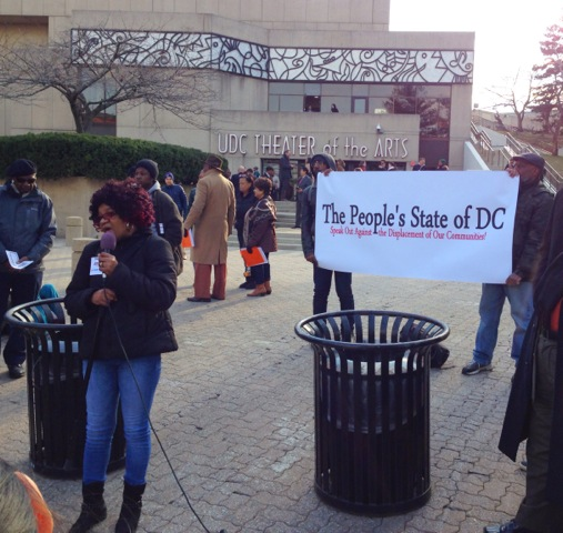 Photo of a woman speaking into a microphone, in front of the UDC Theater for the Arts and with a banner reading