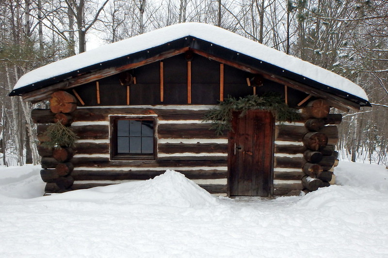 Snow-covered log building with greenery over the door.