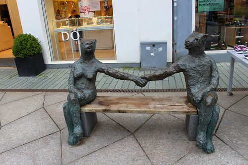 two statues holdings hands on bench