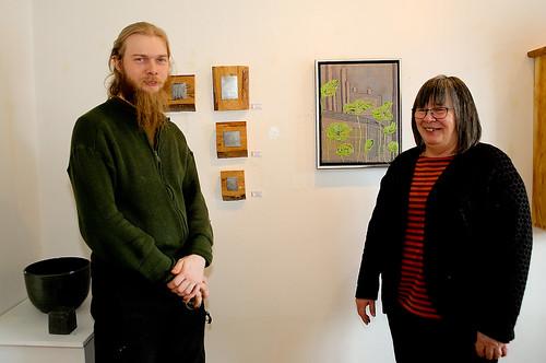 Anders Fredin med några av sina konstverk i etsad stålplåt och Lena Neander som bara visar ett verk i vårens utställning, ett broderi med grönskande träd och hus i bakgrunden.