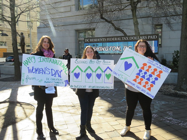 Three young women holding signs about International Women's Day and the need for safe housing for survivors of domestic violence. They stand in front of the Wilson Building digital ticker and some of their chalk-work is visible on the sidewalk behind them.
