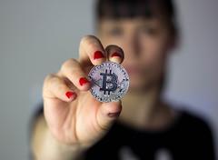 Girl holding silver Bitcoin