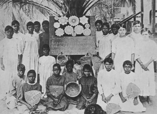 Mapoon workers displaying handmade crafts and a presentation set of lace d'oyleys, 1916
