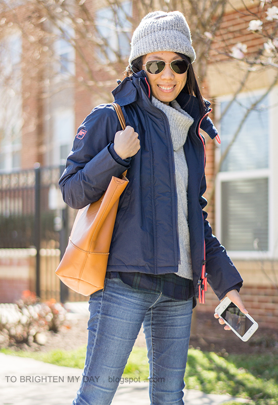 gray beanie, navy windcheater jacket, gray turtleneck sweater over black watch plaid shirt, skinny jeans, cognac tote