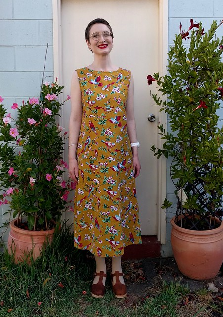 A woman stands in front of a garage, wearing a slightly a-line, midi length sleeveless dress in mustard with floral bird print.