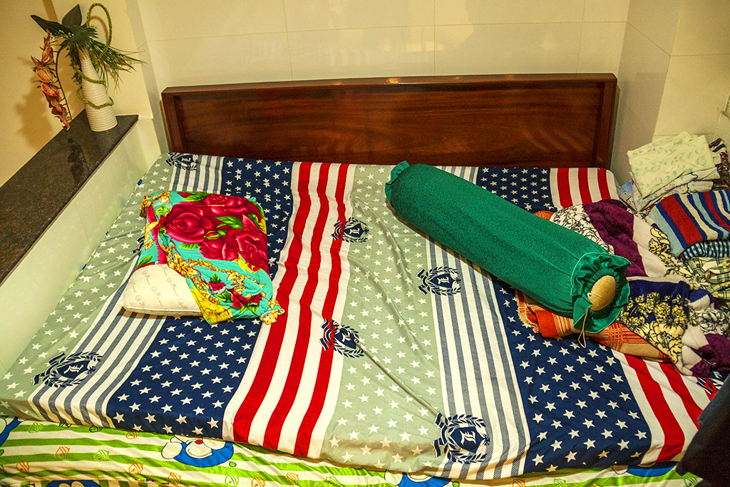 Stars and Stripes bed sheet on old man's bed--Saigon
