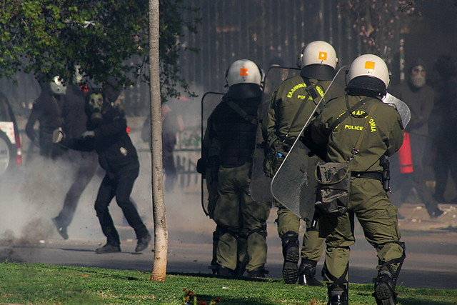 Rioter prepares to throw a piece of broken paving stone at riot police