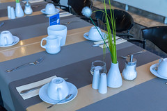 Table ready laid with coffee mugs and silverware