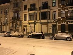 Voitures parquées sous la neige le long des belles façades
