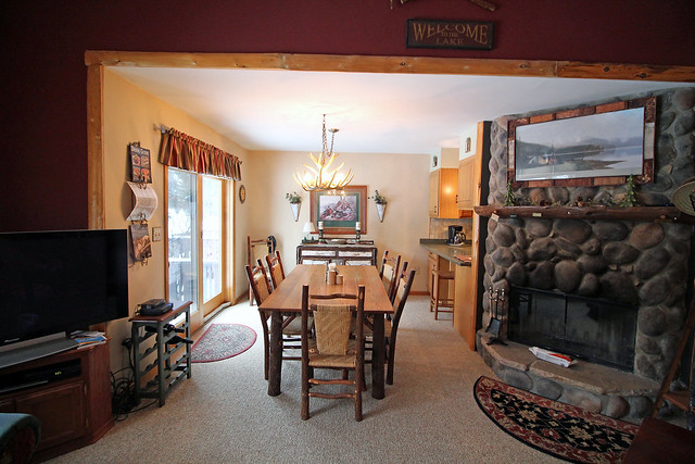Looking into the dining area from the living area. Stone fireplace with kitchen to your right of the photo