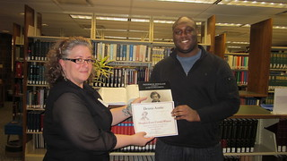 Tue, 12/04/2018 - 04:01 - Dennis Austin receiving his prize from Jessica Olin, director of the Alfred C. O'Connell Library, courtesy of GCC