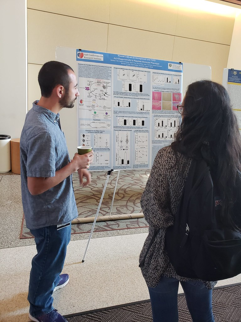 Zach Hilt explains his cardiovascular research to a fellow peer