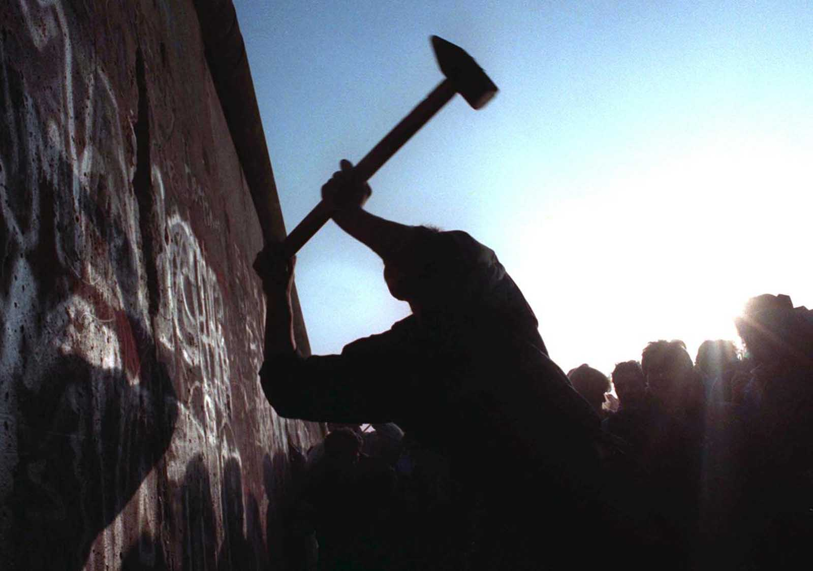 A man hammers away at the Berlin Wall on November 12, 1989, as the border barrier between East and West Germany is torn down.
