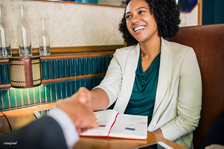 Woman shaking hands with business partner | by Rawpixel Ltd