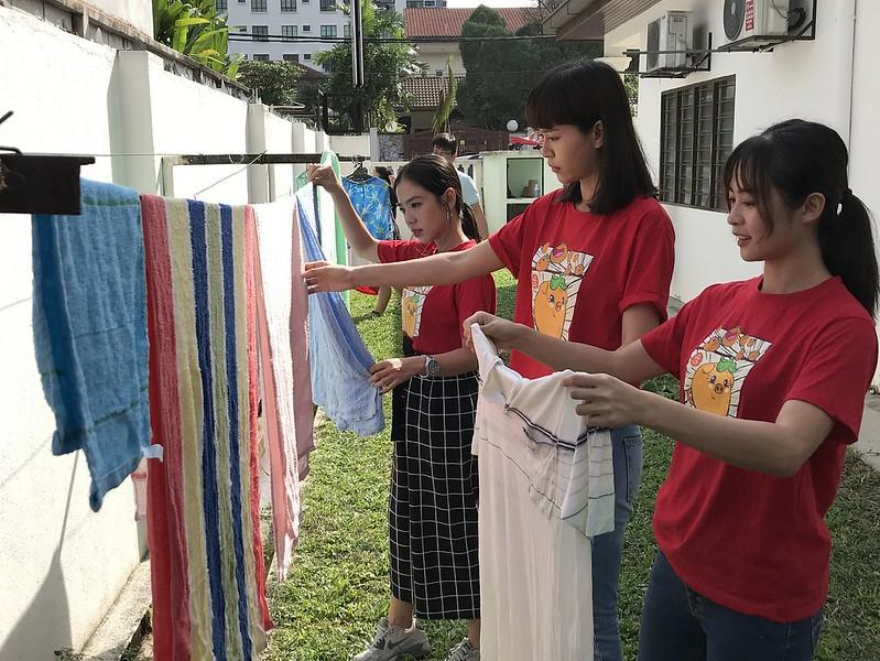 Chrystina Ng, Lynn Lim dan Happy Gan menolong untuk sidai kain di En Yuan Old Folk Home