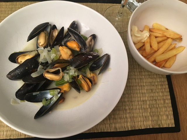 A large bowl of mussels in sauce with a small bowl of chips next to it.