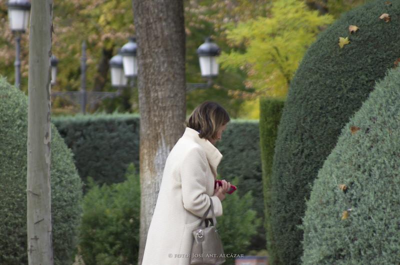 Mujer paseando por un parque, entre árboles y arbustos