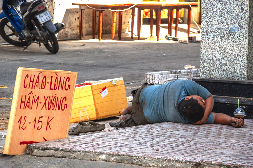 Man lying on a Phu Lam sidewalk--Saigon