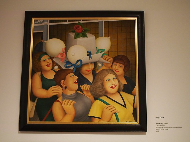 The painting 'Hen Party' by Beryl Cook showing five plump happy looking women carrying handbags. The woman in the middle has a large white box shaped hat on her head which looks like a wedding cake and has three white boob-shaped balloons attached with coloured ribbons