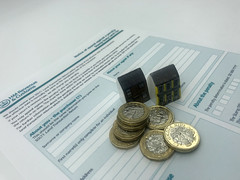 Houses, £1 sterling coins and a HMRC Stamp Duty Land Tax form