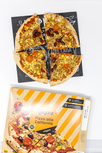 Vegane Pizza mit Bohnen, Mais und Tomaten auf Schieferplatte neben Pizzakarton vor weißem Hintergrund