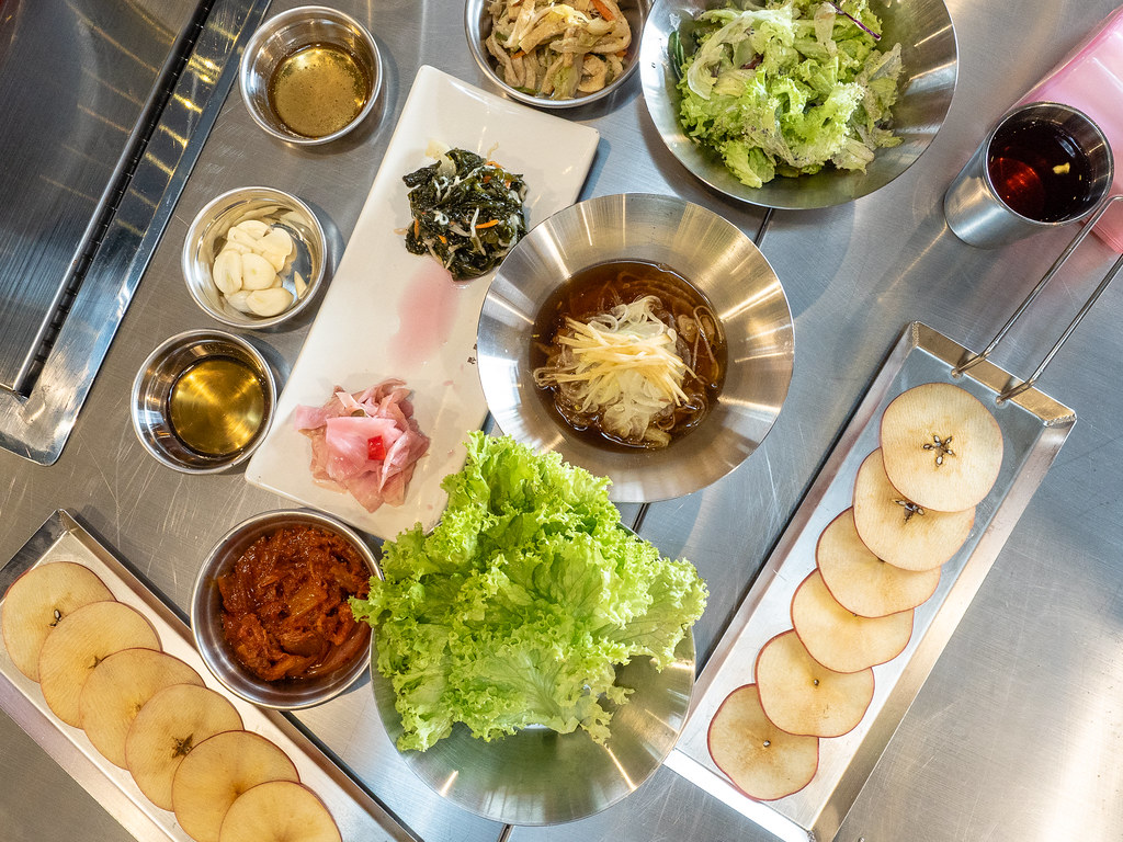 Overview of Apple Samgyupsal's banchan, vegetables and apple slices