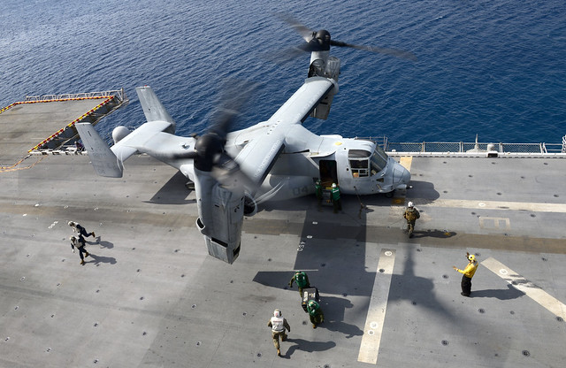 """PHILIPPINE SEA (Jan. 18, 2019) Flight deck crewmembers unload equipment and supplies from an MV-22 Osprey assigned to the """"Flying Tigers"""" of Marine Medium Tiltrotor Squadron (VMM) 262 aboard the amphibious assault ship USS Wasp (LHD 1). Wasp, flagship of the Wasp Amphibious Ready Group, with embarked 31st Marine Expeditionary Unit, is operating in the Indo-Pacific region to enhance interoperability with partners and serve as a ready-response force for any type of contingency. (U.S. Navy photo by Mass Communication Specialist 1st Class Daniel Barker)"""